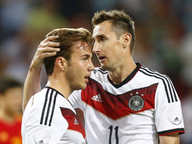 PASSING THE BATON: 36-year-old Miroslav Klose (right) embraces 22-year-old Mario Gotze, his replacement, who went on to score the winning goal to give the German legend a resounding send-off in what will surely be his final World Cup appearance. (Photo: Ralph Orlowski/Reuters)