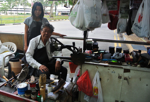 FATHER-DAUGHTER DUO: In their corner at the Yishun bus interchange, they fix broken soles for a living. (PHOTO: Cheryl Wong)