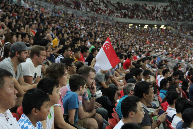 FIRST OF MANY: A solitary flag among the crowd. Perhaps, when Singapore regains the Kallang Roar, we might see a whole stadium waving their flags in unison. (Photo: M. Shanjayan))