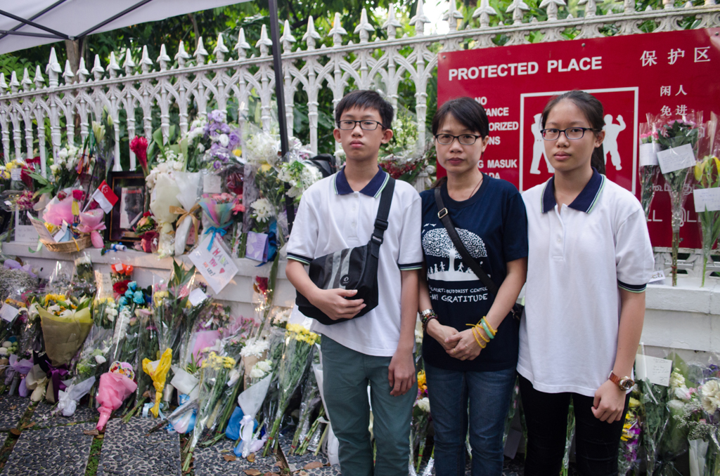 A LESSON FOR ALL: (From left) Ming Yang, Jean Er and Wei Lin stand in front of a row of gifts left by the mourning visitors. Jean wanted to teach her  children something about Mr Lee, so she decided to bring both of  them down to the Istana on Tuesday, where Mr Lee lay inside during a private wake. The trio wrote condolence cards and left a bunch of flowers. (Photo: Marcus Tan)
