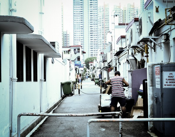 "MODERNISATION: The only constant in this world is change.The edifice in the background is a stark contrast to the shophouses that the residents in Tiong Bahru used to see. Some cope with modernisation by collecting ""memories"" left behind in garbage bins and old cardboard boxes. (Photo: Sariyanto Slamat)"