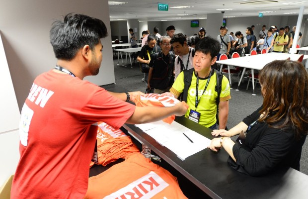 PASSING THE BIBS: Year 1 DMC student Azmi Athni distributes the official photographer bibs to photojournalists in the media centre. (Photo: World Sport Group)