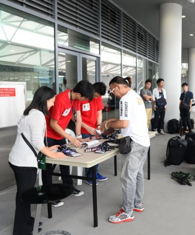 HARD AT WORK: Year 2 DMC students Dzulfikaar Sutandar (2nd L) and Ken Lu, along with other volunteers, sort out the various passes for the media. (Photo: World Sport Group)
