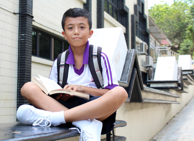 QUIET SANCTUARY: Muhd Farzad, 11, unwinds after a long day at school by reading a book along the walls of the mosque. The serenity and peace in the area is what attracts him here. (Photo: Emmanuel Phua)