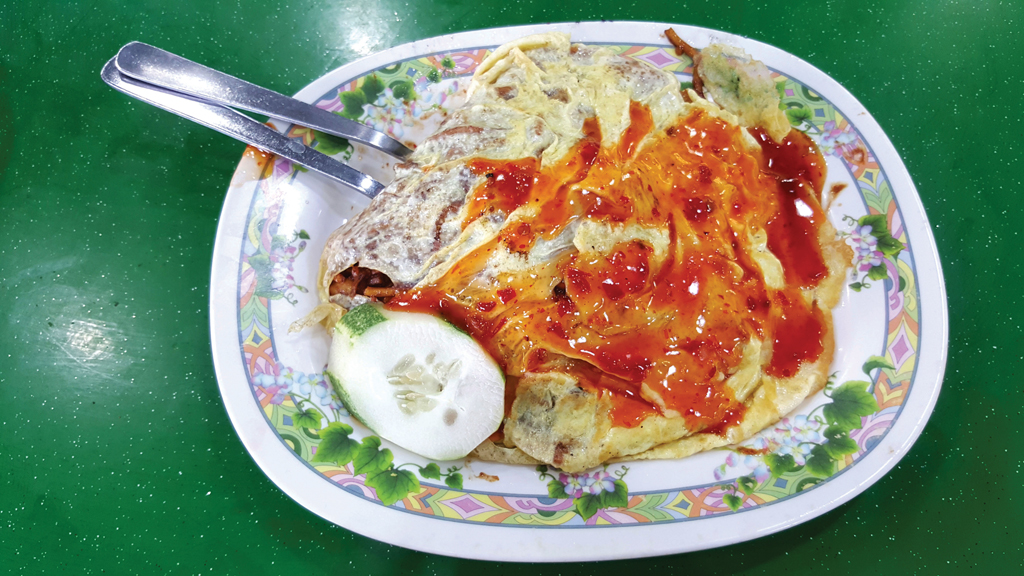 Hearty Meal: The mee goreng pattaya has yellow noodles buried in a warm fried egg duvet.