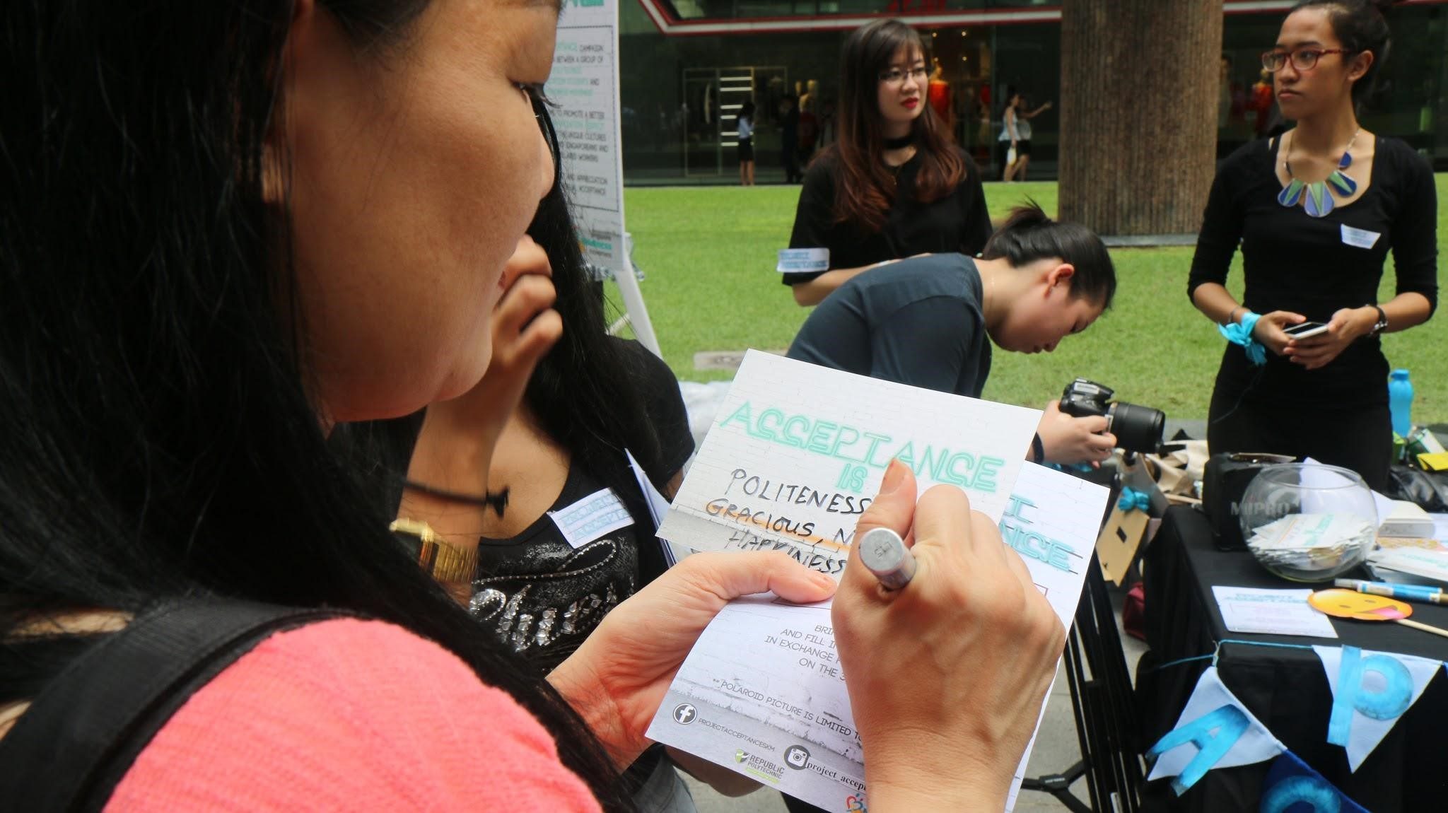 REFLECT: A booth was set up at Zoysia Green, Raffles Place Park on Aug 3, 2016 to encourage the lunch crowd at Zoysia Green, to reflect on and pen down what acceptance means to them in the context of social integration on a Acceptance card. (Photo: Joan L Koh Jia Min)